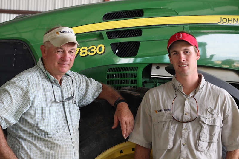 Two workers in front of John Deere tractor