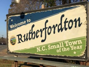 Rustic road sign that reads: Welcome to Rutherfordton: N.C. Small Town of the Year