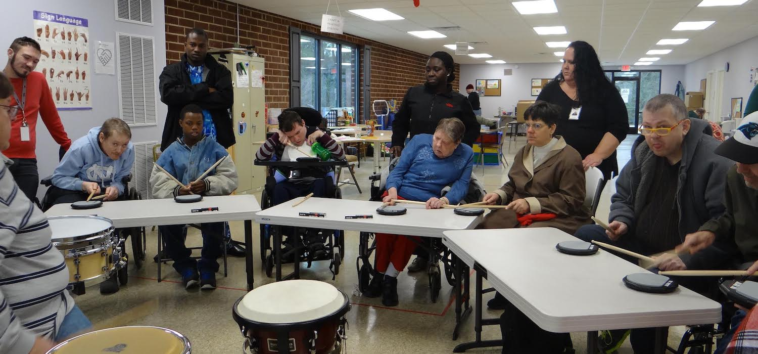 Participants having fun learning to drum on electric drums at Servant's Heart